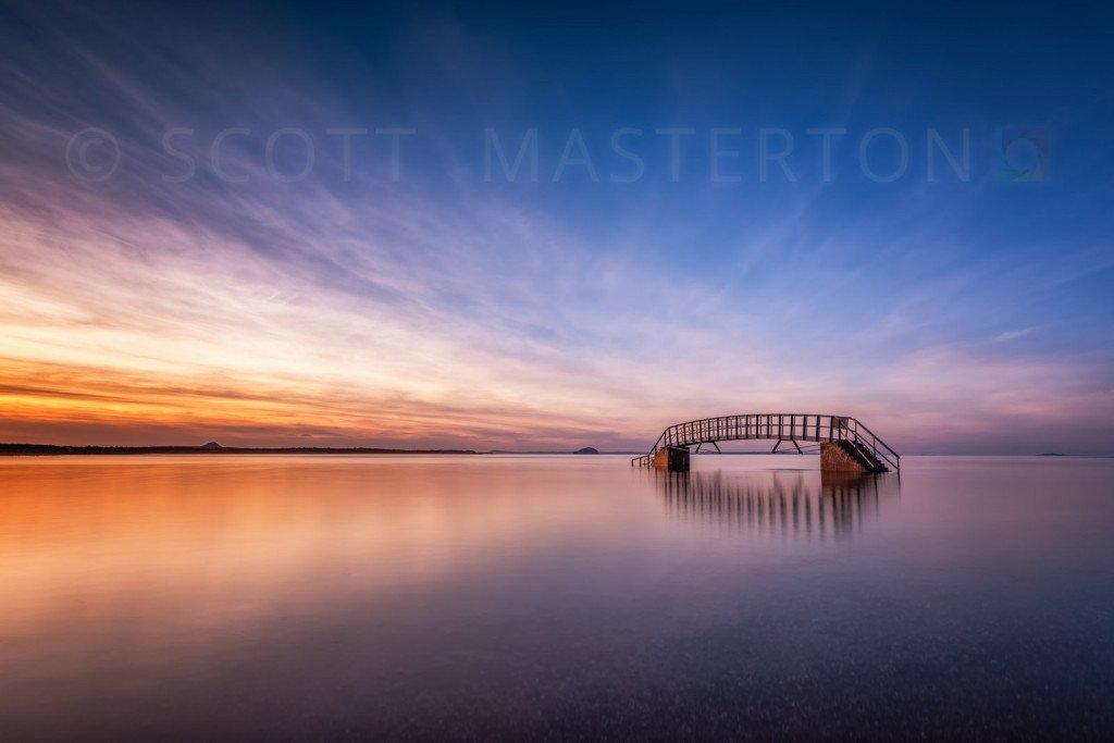 Sunset with Belhaven Bridge (The Bridge to Nowhere) at high tide, Belhaven, Dunbar, East Lothian, Scotland, UK.